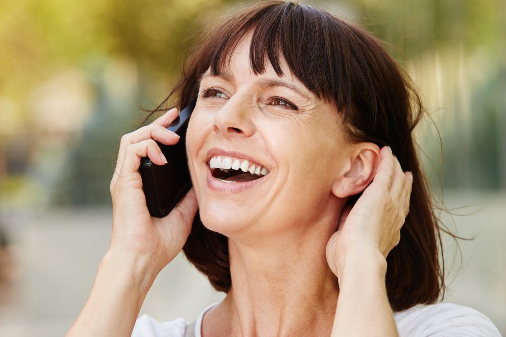 A happy looking woman making a mobile phone call