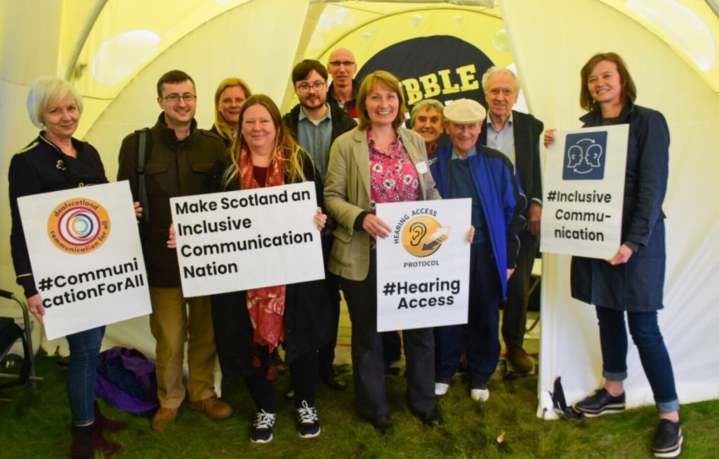 A group of people with placards that read: Make Scotland an Inclusive Communication Nation, hashtag Hearing access, hashtag Inclusive Communication and hashtag communication for all