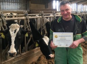 A farmer holds a certificate with black and white cows behind him