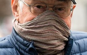 An older man wearing a scarf that is pulled up over his mouth and nose