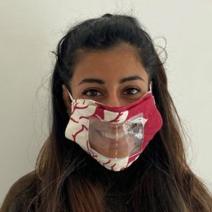 A woman wears a red and white mask with a clear panel