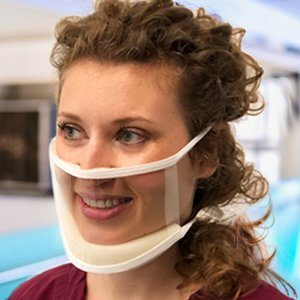 A woman wears a mask that is completely clear, except for a white fabric trim round the edge and comfort stuffing
