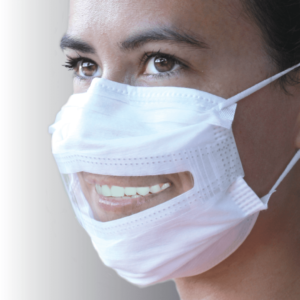 A woman wears a white surgical mask with a clear panel. She is side on to the camera and smiling