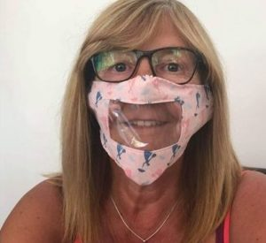 A woman wears a pink mask that has a clear panel. She is looking at the camera and smiling.
