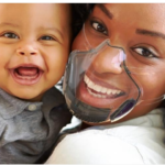 A laughing woman holding a child is wearing a complete transparent mask. It looks like it might be made of clear plastic.