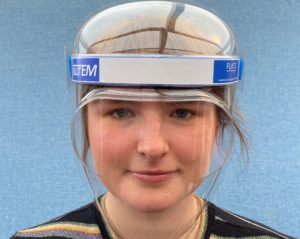 A young woman wears a plastic see-through face shield