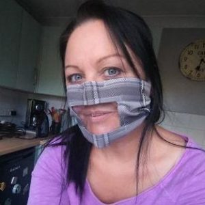 A woman wears a grey fabric mask that has a clear panel.