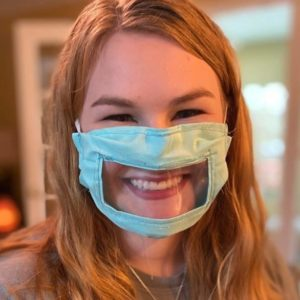 A young woman with long fair hair and wearing a green mask with clear panel smiles at the camera.