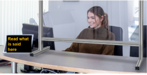 A woman sits behind a plastic screen. In front of her is a digital screen display subtitles
