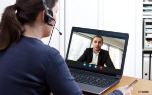 A woman with a headset speaks to a man on a video call