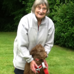 An older lady with with a brown dog is smiling at the camera